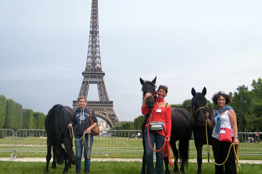 Des propriétaires Alegria avec leurs chevaux devant la Tour Eiffel à Paris
